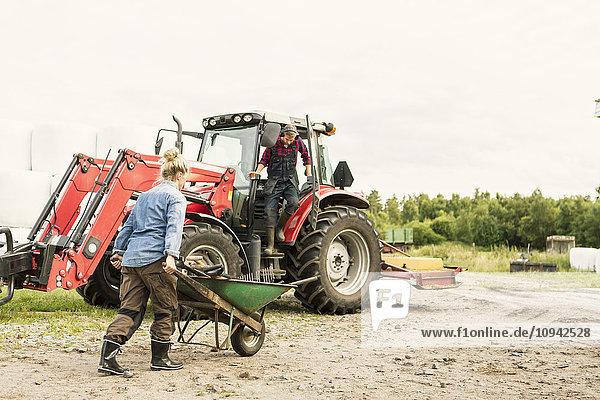 Frau schiebt Schubkarre zu Mann und Traktor auf dem Bauernhof