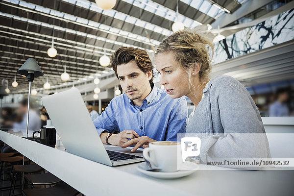 Geschäftskollegen mit Laptop im Flughafencafé