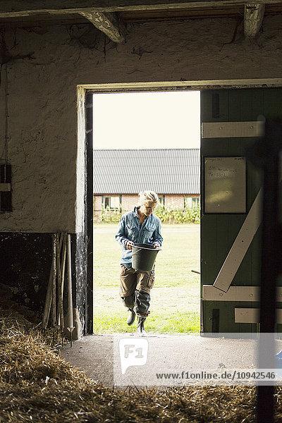 Frau hält Eimer beim Betreten der Scheune auf dem Bauernhof