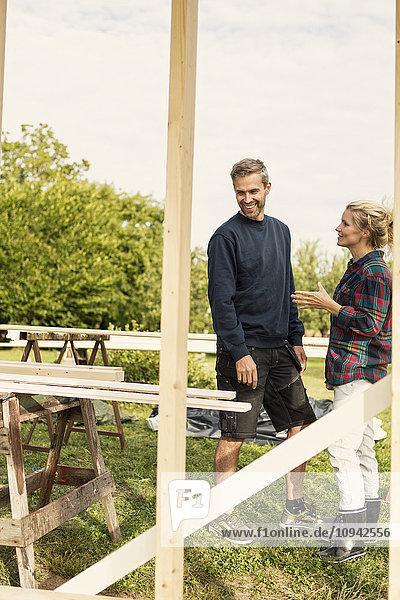 Ein glückliches Paar  das auf dem Bauernhof über Holzbretter diskutiert.