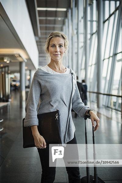 Portrait einer selbstbewussten Geschäftsfrau mit Gepäck am Flughafen Portrait einer selbstbewussten Geschäftsfrau mit Gepäck am Flughafen