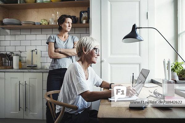 Industriedesigner mit Laptop am Tisch und Kollegen in der Küche