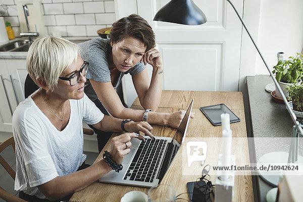 High-Winkel-Ansicht von Produktdesignern  die über den Laptop zu Hause diskutieren.