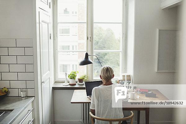 Rückansicht des Industriedesigners mit Laptop am Tisch am Fenster