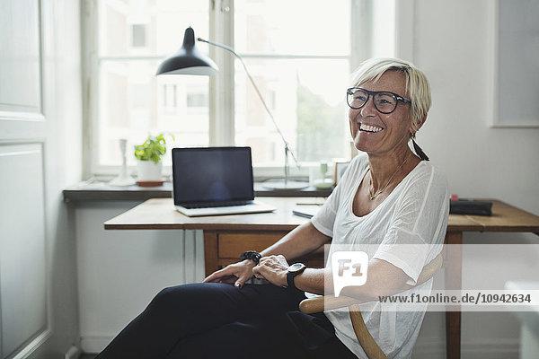 Glücklicher Industriedesigner schaut weg  während er zu Hause im Büro sitzt.