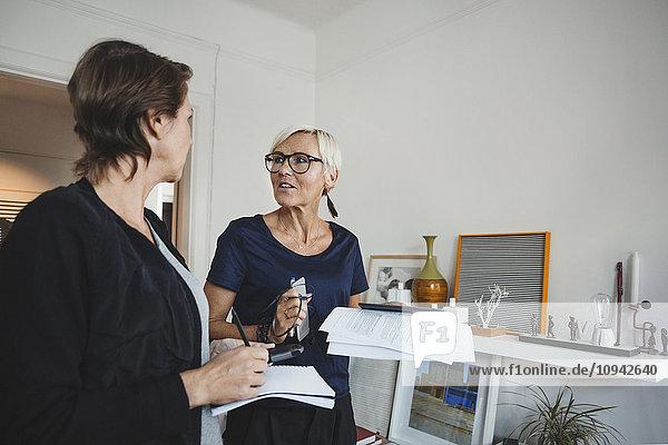 Produktdesigner halten Dokumente bereit  während sie zu Hause diskutieren.