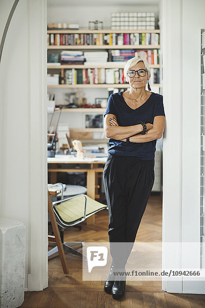 Full length portrait of confident designer standing arms crossed at home