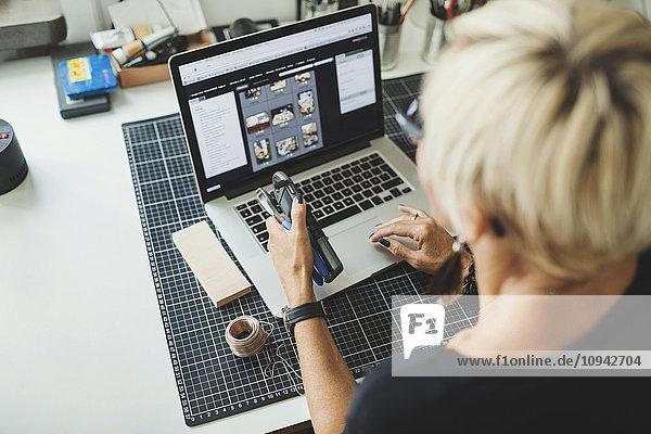 High-Winkel-Ansicht des Industriedesigners mit Laptop  während er das Produkt im Home-Office hält.