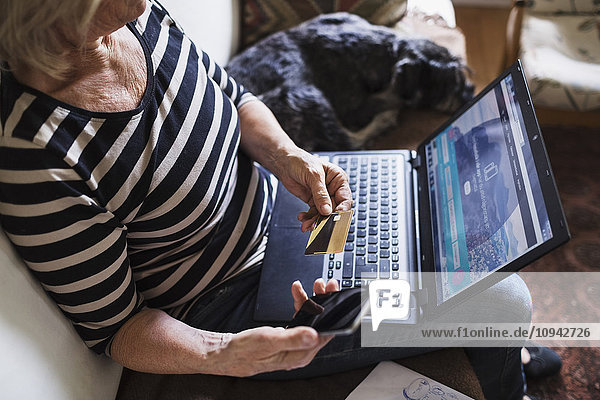 Hochwinkelansicht der Seniorin mit Technik und Kreditkarte beim Sitzen mit Hund auf dem Sofa