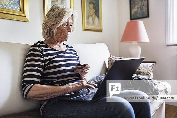 Seniorin beim Online-Shopping  während der Hund sich zu Hause auf dem Sofa entspannt