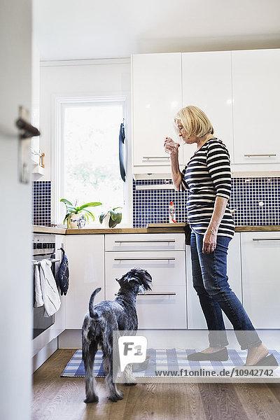 Seniorin trinkt Wasser im Stehen in der Küche