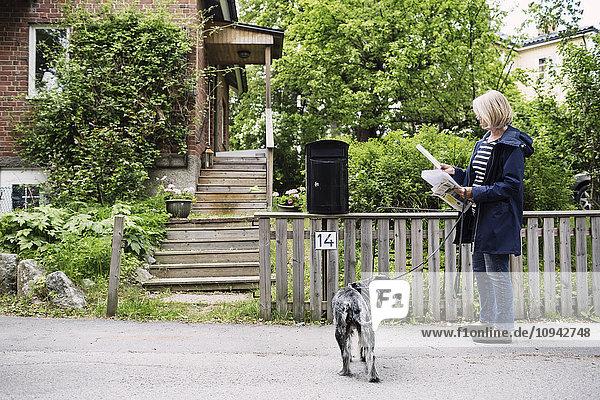Seniorin prüft Briefe im Stehen mit Hund vor dem Haus