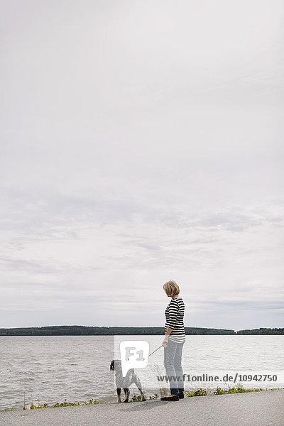 Seitenansicht der Seniorin mit Hund am Seeufer vor dem Himmel