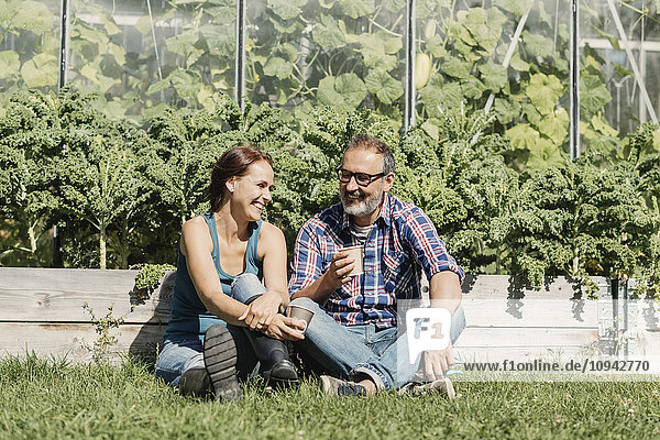 Glückliche Bauern genießen Kaffeepause auf Gras gegen Gewächshaus