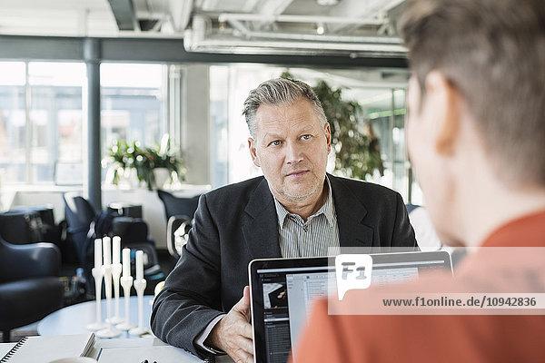 Geschäftsmann  der während des Treffens einen Kollegen ansieht