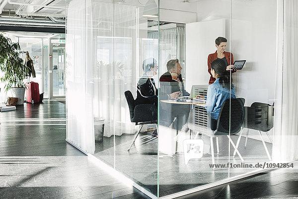 Geschäftsfrau zeigt Kollegen digitales Tablett durch Glas gesehen