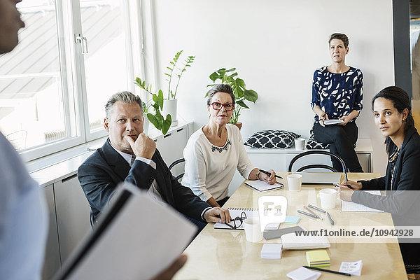Geschäftsleute  die während der Besprechung im Büro einen männlichen Kollegen anschauen