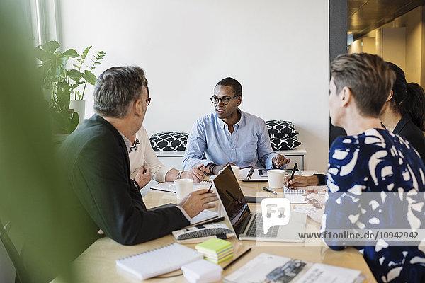 Multiethnische Geschäftsleute diskutieren im Büro