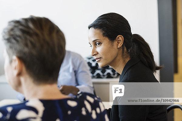 Geschäftsfrau  die während der Besprechung im Sitzungssaal eine Kollegin ansieht
