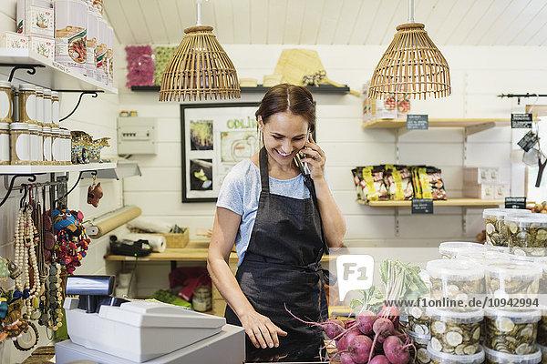Fröhliche Frau beim Telefonieren am Ladentisch im Geschäft