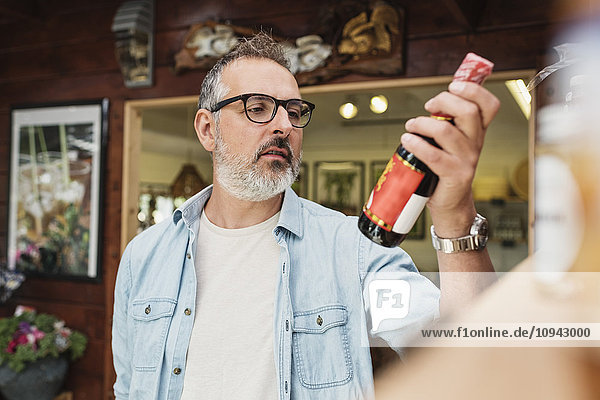 Reifer Mann  der beim Einkaufen im Geschäft Informationen über die Flasche prüft.