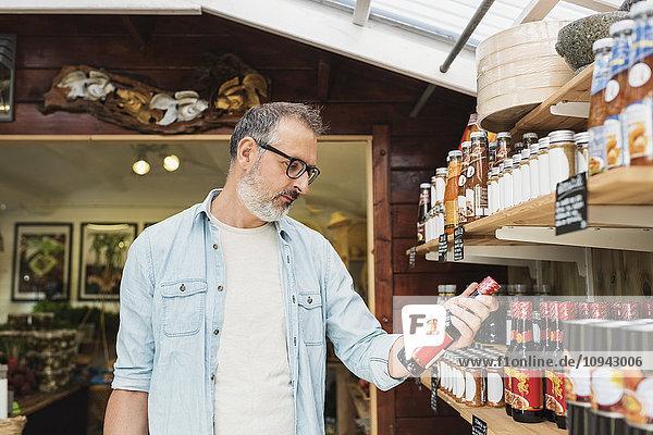 Reifer Mann beim Einkaufen in der Flasche