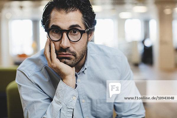 Porträt eines Mannes mit Hand am Kinn sitzend am Flur