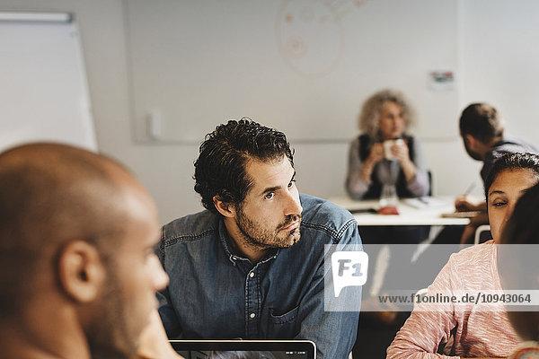 Freunde diskutieren  während ein Mann mit einem Lehrer im Sprachkurs sitzt.