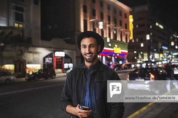 Porträt eines glücklichen Mannes  der ein Smartphone hält  während er nachts auf der Straße steht.
