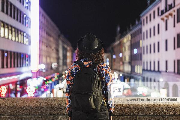 Rückansicht der Frau mit Rucksack auf der Brücke in der Stadt bei Nacht