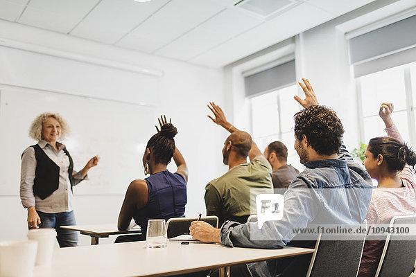 Schüler mit erhobenen Armen betrachten Lehrer in der Sprachklasse