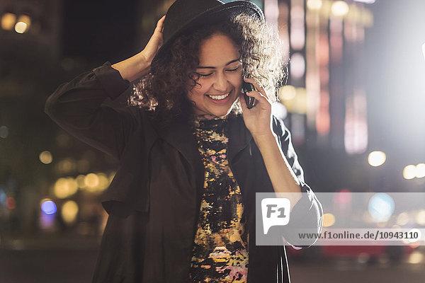 Fröhliche junge Frau  die nachts in der Stadt ans Smartphone geht
