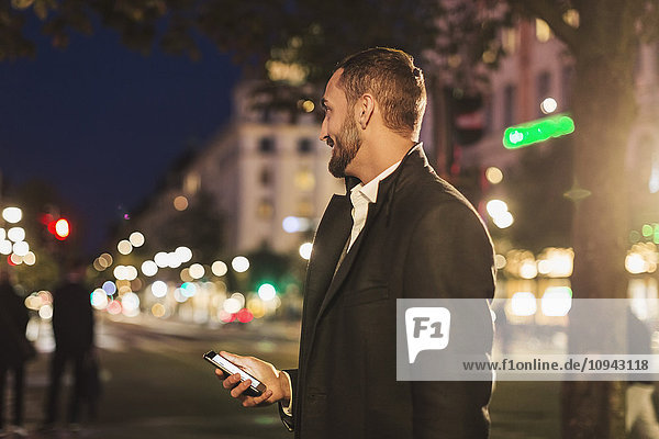 Side view of man looking away while holding smart phone on city street at night