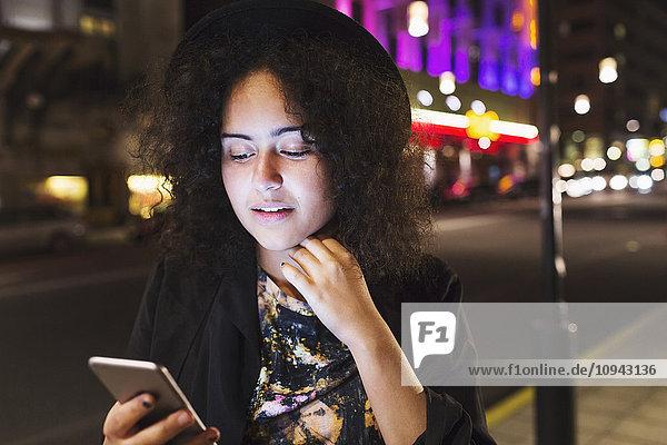 Woman using smart phone sidewalk in city at night