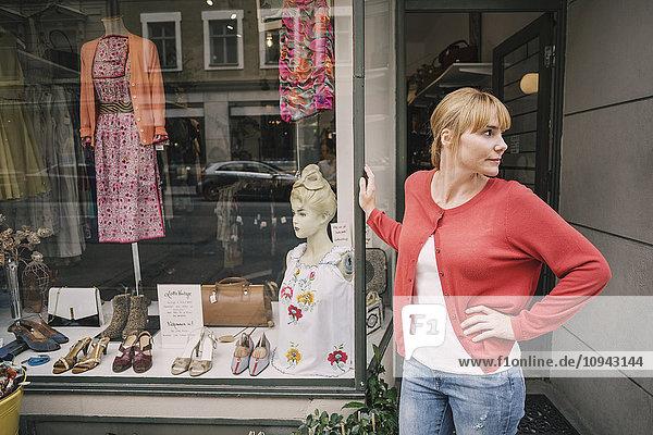 Zuversichtlicher Besitzer  der mit der Hand auf der Hüfte gegen den Laden steht.