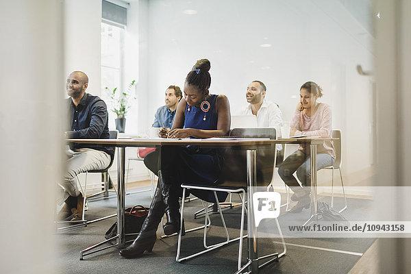 Schüler sitzen im Sprachunterricht durch Glas gesehen