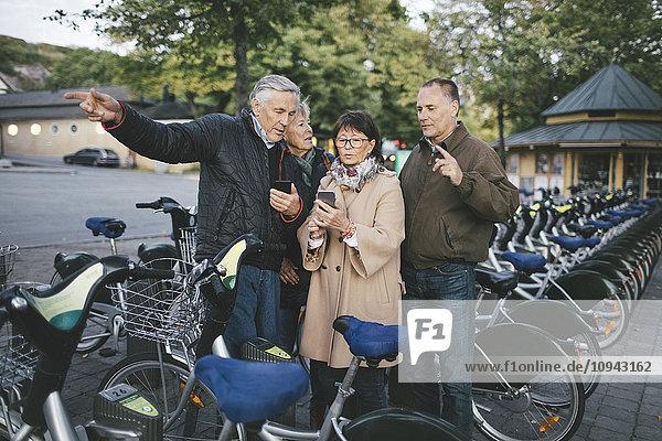 Seniorenpaare mit Mobiltelefonen am Fahrradabstellplatz
