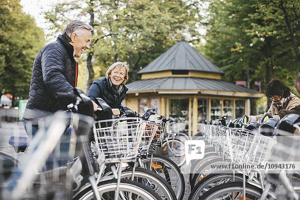 Senioren mit Leihfahrrädern auf dem Parkplatz
