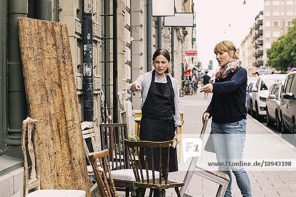Besitzer und Kunde  der auf einen Stuhl außerhalb des Antiquitätengeschäfts zeigt.