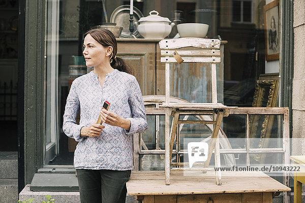 Frau schaut weg  während sie neben Stuhl und Tisch vor dem Laden steht. Frau schaut weg, während sie neben Stuhl und Tisch vor dem Laden steht.