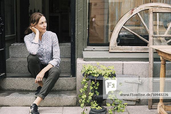 Nachdenkliche Besitzerin auf einer Treppe im Laden sitzend