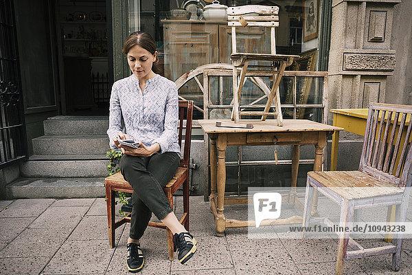Frau  die das Handy benutzt  während sie auf dem Stuhl gegen den Laden sitzt.