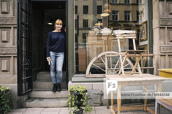 Besitzerin steht am Eingang des Antiquitätengeschäftes