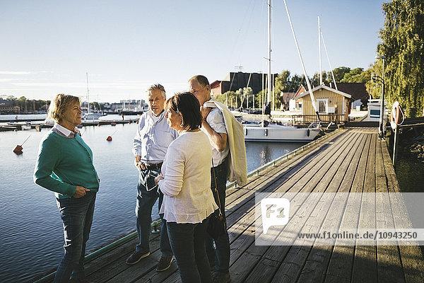 Zwei ältere Paare  die auf dem Pier stehen und sich unterhalten.