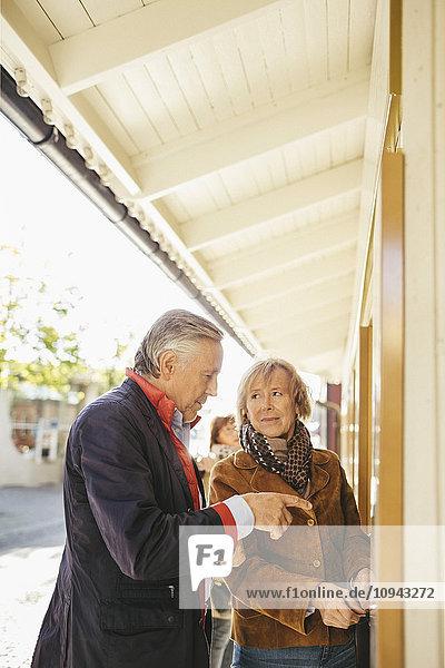 Glückliches Seniorenpaar beim Kartenkauf im Musiktheater