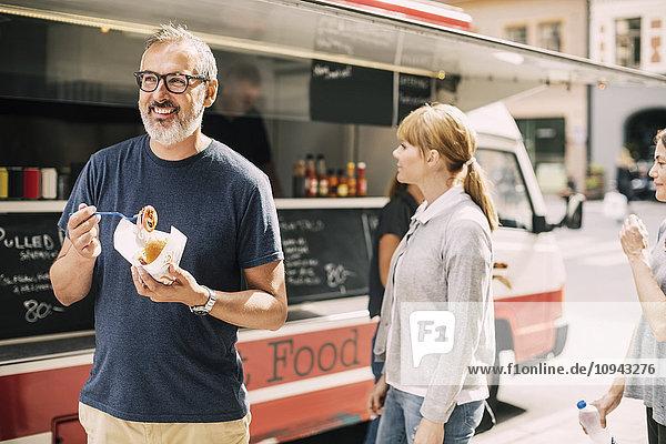 Erwachsener Mann  der Essen isst  während er auf der Straße gegen den Lastwagen steht.