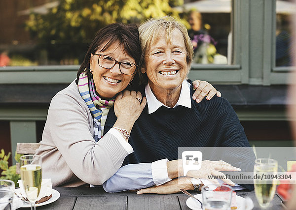 Lächelnde Senioren-Freundinnen mit Arm am Kaffeetisch