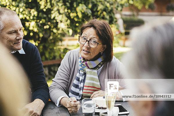 Seniorin im Gespräch mit Freunden am Kaffeetisch