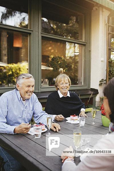 Lächelnder älterer Mann mit weiblichen Freunden beim Dessert im Außenrestaurant