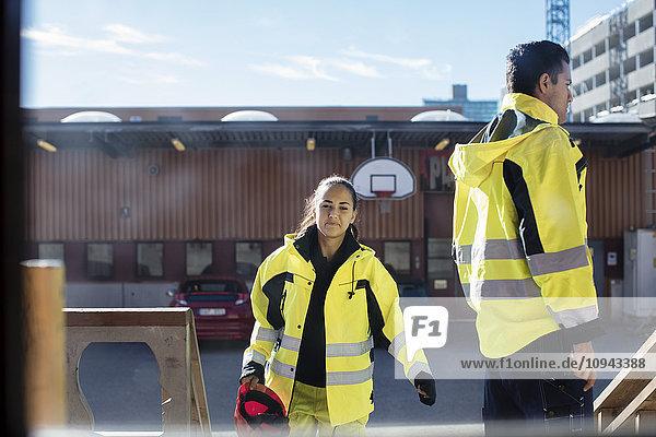 Lächelnde Automechanikerin mit männlichem Freund durchs Glasfenster gesehen